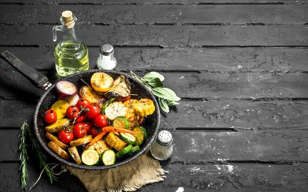 Жареные овощи на сковороде с травами и специями на темном деревенском столе.