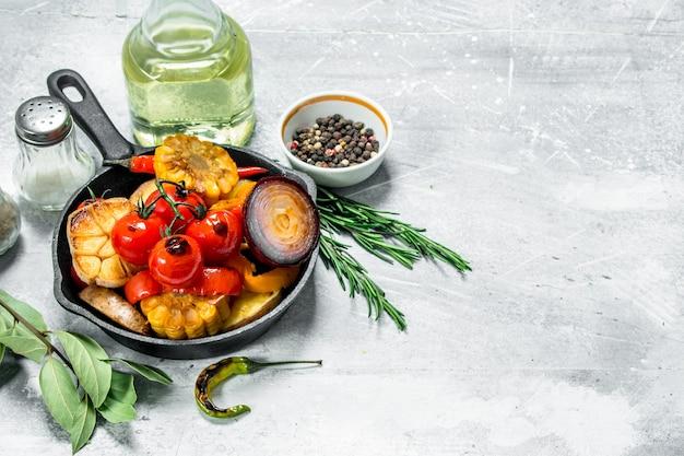 Овощи гриль на сковороде со специями. на деревенском столе.