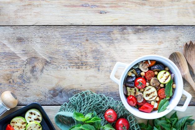 素朴な背景に食材を使った白いセラミック鍋で焼いた野菜。ベジタリアンフード。上面図。コピースペース