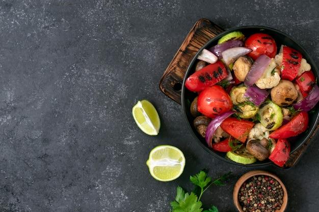 黒の背景に野菜のグリル。ビーガンメニュー。プレートの野菜ミックス