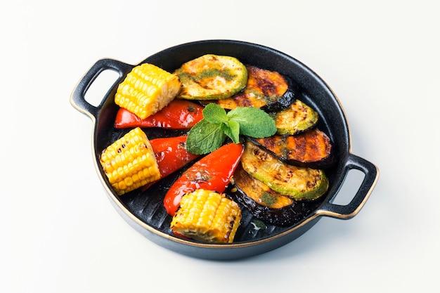 Жареные овощи на тарелке на белой поверхности.