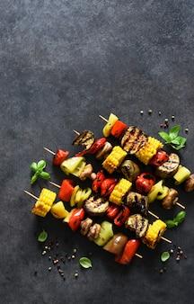 Овощи-гриль на шпажке на черном фоне бетона вид сверху
