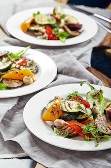 Жареные овощи на белых тарелках. ресторанное блюдо