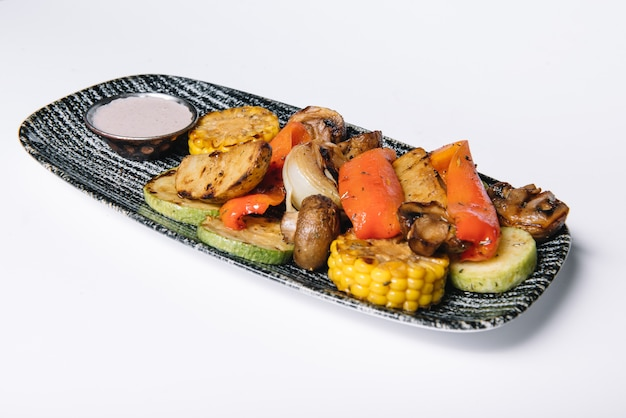 흰색 배경에 고립 된 커팅 보드에 구운 된 야채