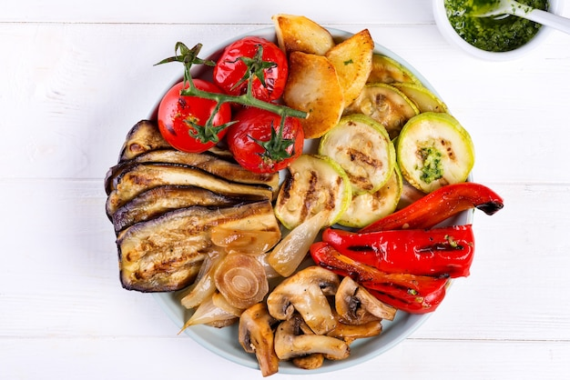 Grilled vegetables on a plate with pesto on white wood
