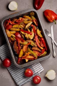 회색 배경에 호박, 가지, 고추, 토마토와 구운 야채 샐러드