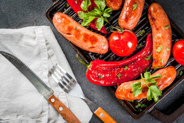 Grilled vegetables and sausages on a grilled baking sheet with spices and herbs.