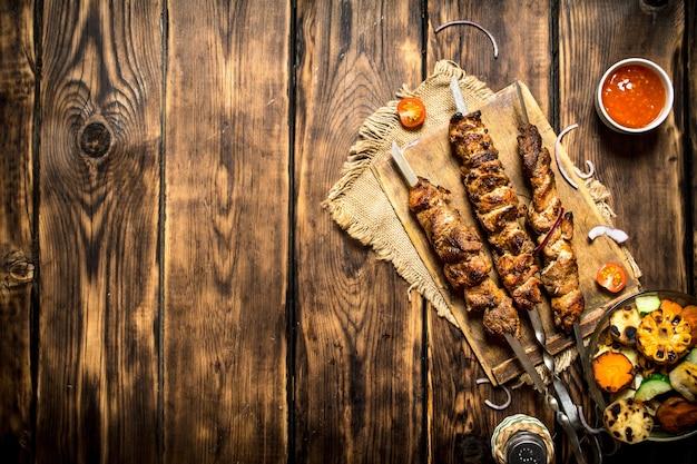 マトンの香りのよいシシカバブを添えた野菜のグリル。木製の背景に。