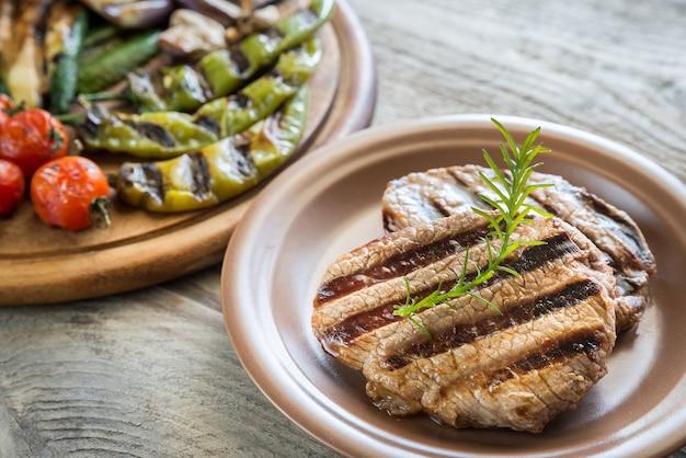 Овощи гриль со стейком из говядины на деревянной доске