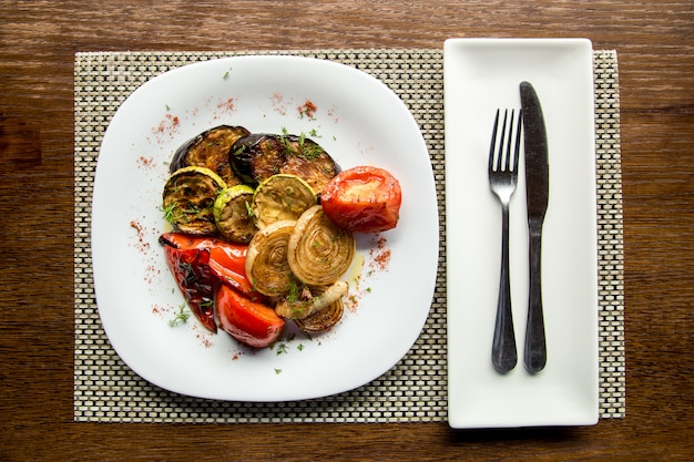 Grilled vegetables with meat in a plate on a wooden table