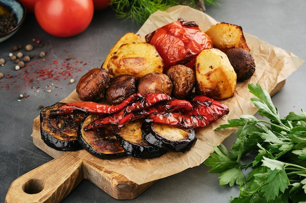 Grilled vegetables on wooden board with parchment