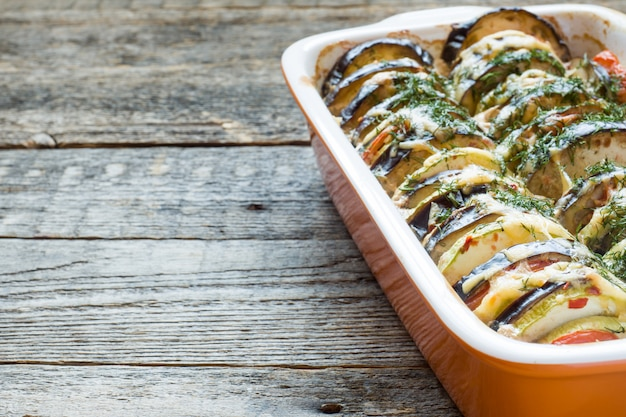 Grilled vegetables zucchini eggplant tomato a kind of ratatouille on a rustic wooden background