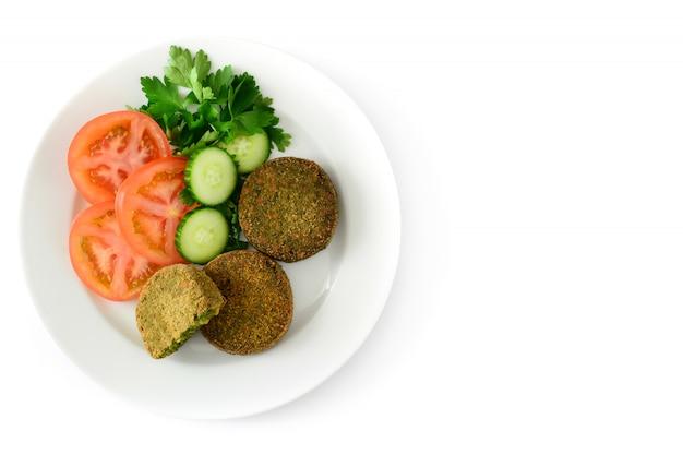 ほうれん草とエンドウ豆のサラダ、白、トップビューで分離された白い皿にサラダと野菜のハンバーガーのグリル