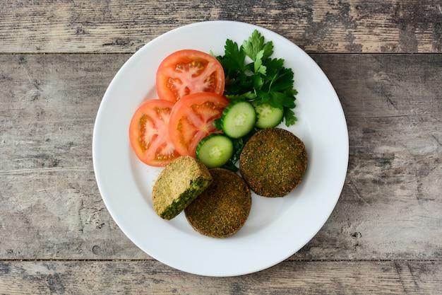 ほうれん草と豆の木製テーブルトップビューで白い皿にサラダと野菜のグリルハンバーガー