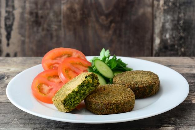 ほうれん草と木製のテーブルの白いプレートにサラダとエンドウ豆のグリル野菜ハンバーガー