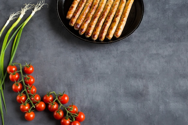Жареные, цельные, вкусные сосиски на сковороде лежали с копией пространства на сером бетонном фоне с двумя ветками свежих помидоров черри и луковыми перьями.