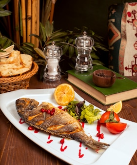 Grilled whole fish with yellow sauce, vegetable salad, lemon and pomegranate seeds in white plate.