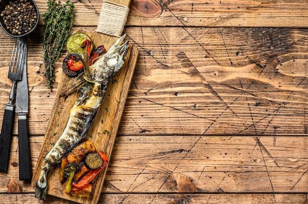 Цельная ледяная рыба на гриле с овощами. деревянный фон. вид сверху. скопируйте пространство.