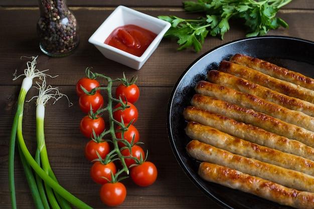 Жареные, целые сосиски на сковороде с веткой свежих помидоров черри, луковых перьев, петрушки и кетчупа в соуснике заделывают на деревянном фоне.