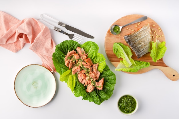 Grilled wild salmon and lettuce dish with green pesto, linen, cutlery, plate, top view