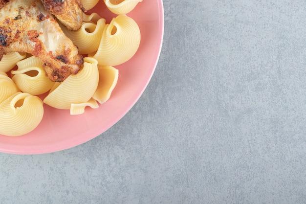 Ali alla griglia e pasta di conchiglie sul piatto rosa.