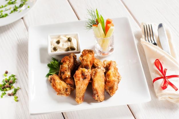 Крылышки на гриле с овощами и столовыми приборами