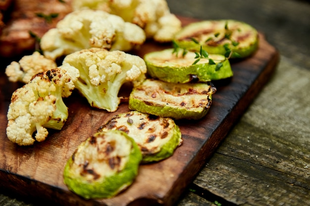 Grilled zucchini and cauliflower vegetable on wooden background . Premium Photo