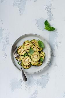 Салат из кабачков на гриле с листьями базилика в простой керамической тарелке на белой бетонной поверхности