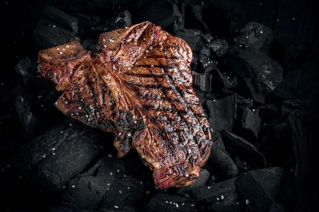 가까이에서 볼 수 있는 석탄에 맛있는 부드러운 절인 티본 스테이크 굽기
