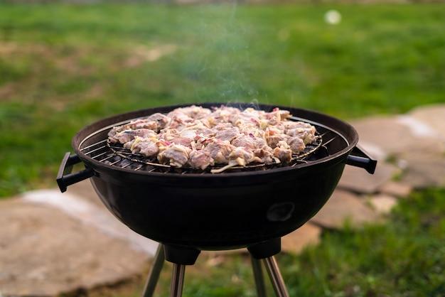 裏庭の屋外グリルでバーベキュー肉を焼く。
