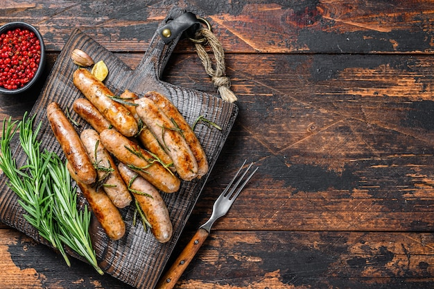 Жарка баварских сосисок на разделочной доске. темный деревянный фон. вид сверху. скопируйте пространство.