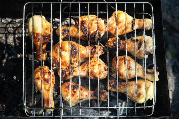 ピクニックで炭火焼きで鶏肉を焼く