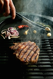 Жарение на гриле стейка рибай в домашних условиях. естественный дым. летний гриль, приготовление пищи в домашних условиях
