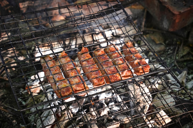 Grilling sausages wrapped becon on  grill