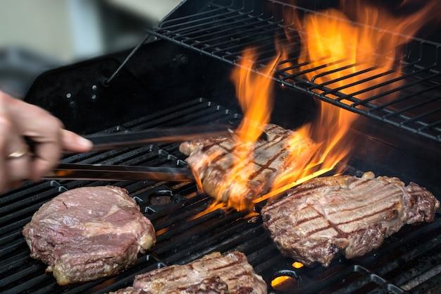 불타는 그릴에 스테이크를 굽고 있습니다. 개념 외부 요리.