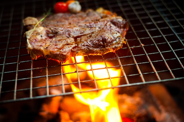 Grilling t bone steak on flaming grill
