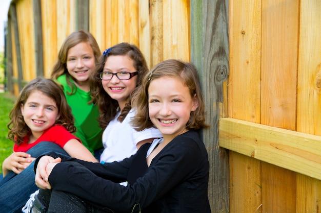 Грильс группа в ряд, улыбаясь в деревянный забор