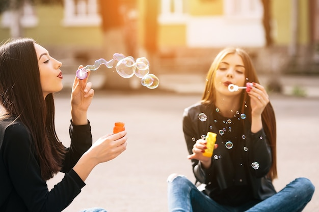 Grils sitting on the floor blowing bubbles