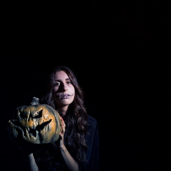 Grim female with scarecrow makeup holding pumpkin