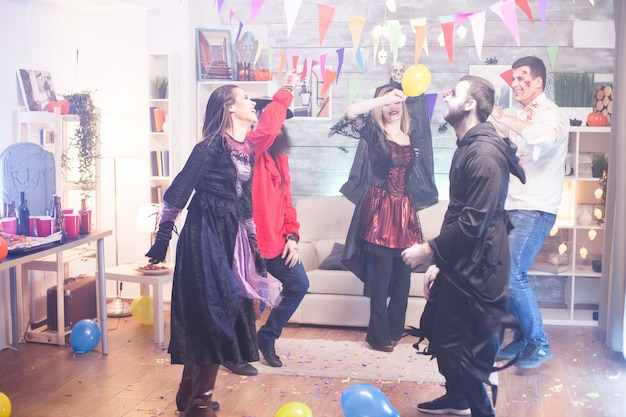 Grim reaper and cheerful witch dancing at halloween celebration. scary costumes.