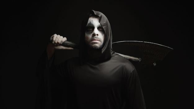 彼の手に斧を持った黒い背景の上の死神。ハロウィーンの衣装。