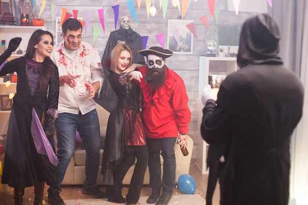 Grim reaper taking photos of pirate and his friends at halloween party.