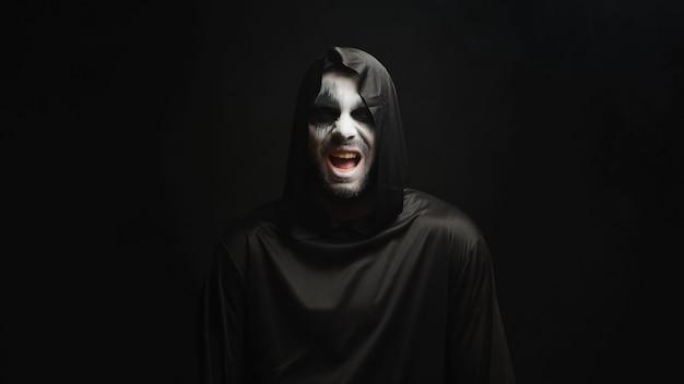 黒い背景の上で怖い笑いを持った死神。不気味な衣装。