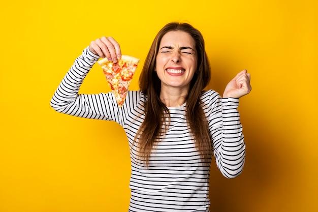 Гримаса косоглазие молодой женщины, держащей кусок свежей пиццы на желтом.