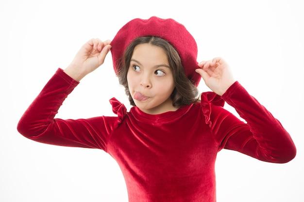 혀로 찡그린 얼굴. 행복한 소녀. 프렌치 스타일의 아이. 베레모를 쓴 파리 소녀. 패션 초상화 귀여운 소녀 유행 모자를 착용. 옷가게. 멋진 액세서리. 패션 개념입니다. 세련된 아이.