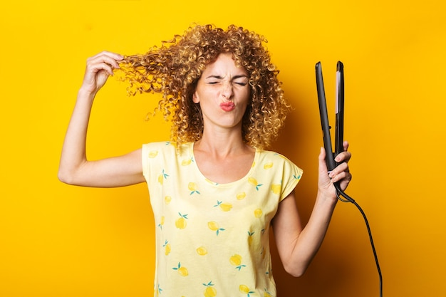 顔をゆがめた若い女性は、黄色の背景にストレートヘアアイロンで巻き毛をまっすぐにします。