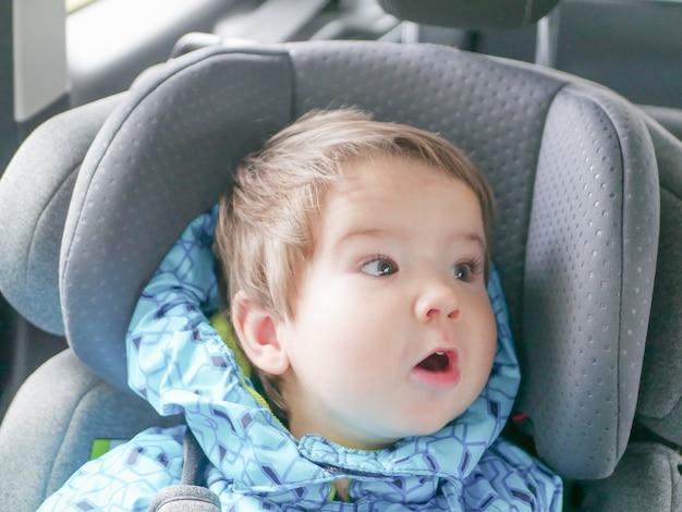 車の座席でしかめっ面の子供。睡眠中のチャイルドシートのチャイルドセーフティ。