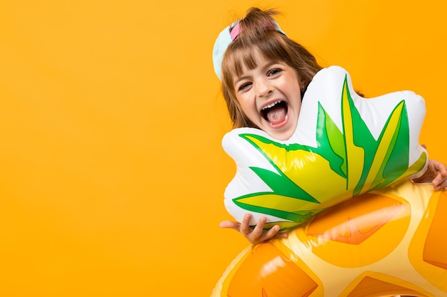 Grimacing girl with a pineapple rubber ring on a yellow background.