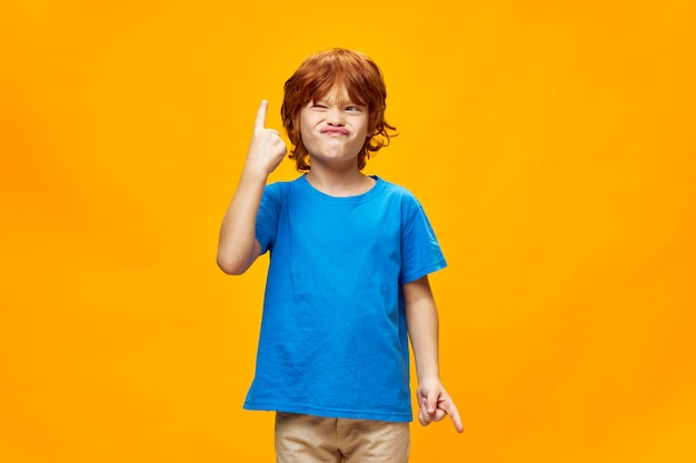 Grimacing red-haired boy looks at the index finger pointing upwards blue t-shirt yellow background copy space