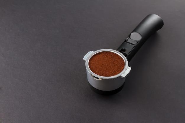黒の背景にコーヒーマシンホルダーで挽いたエスプレッソ